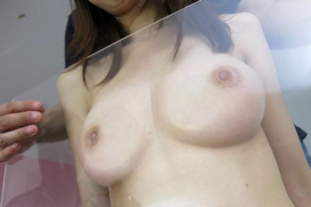 Dカップおっぱいを透明なアクリル板に押し付けている画像